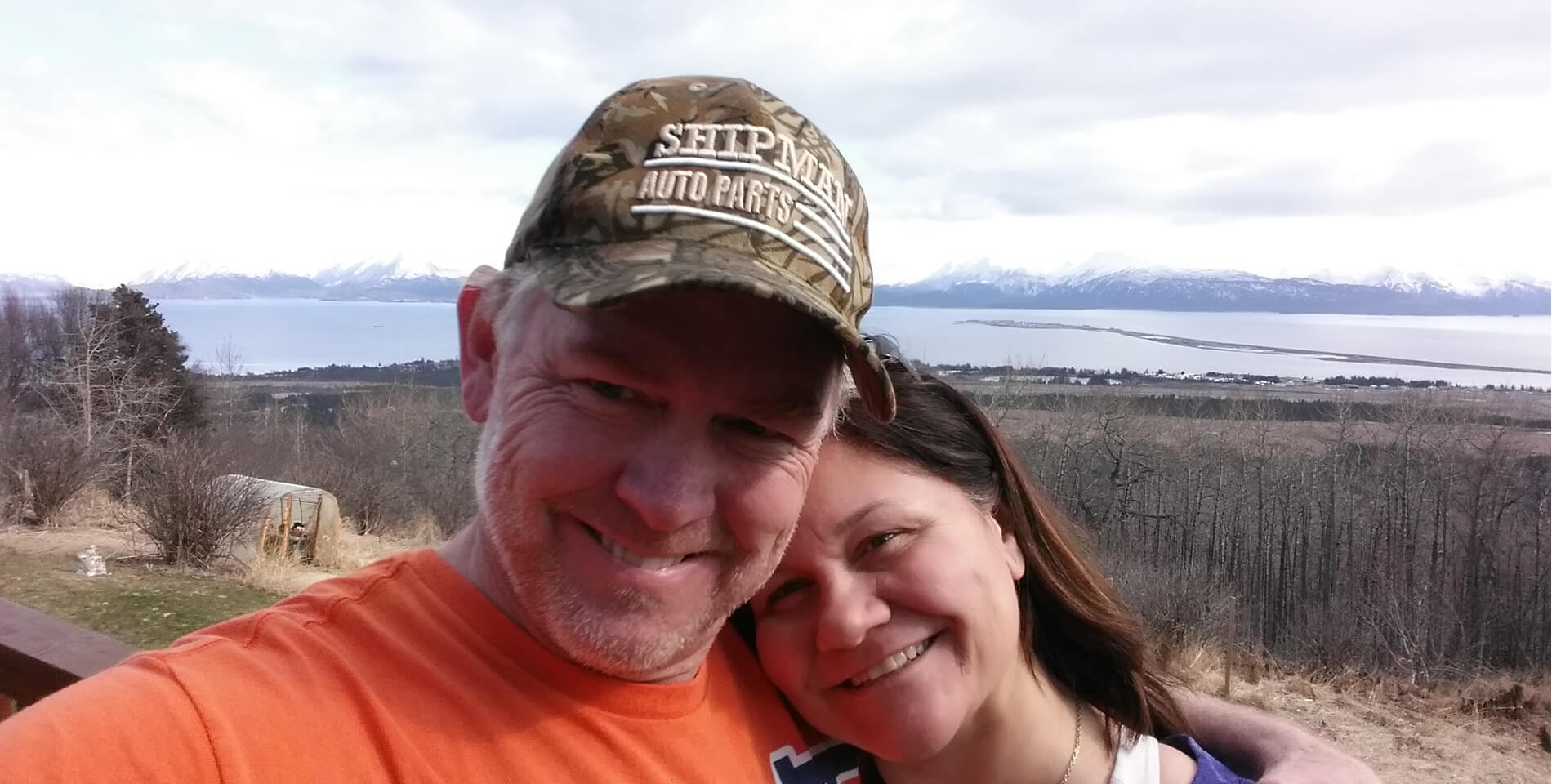 """Shows Maria and Tim taking a """"selfie"""" out on the deck of the main house with the bay, spit and mountains in the background."""