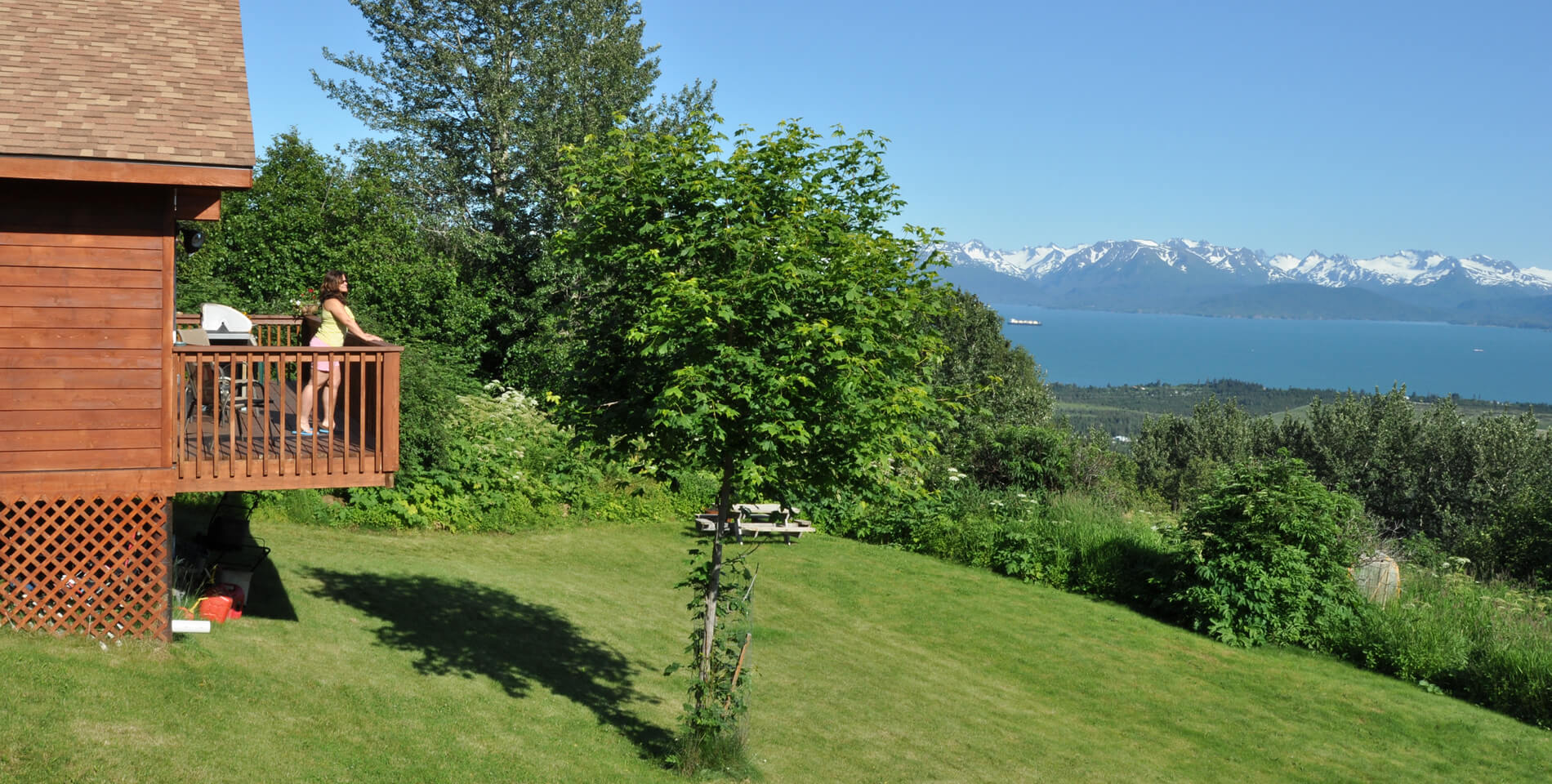 Woman standing on the deck of the cabin enjoying a sunny afternoon, viewing the bay and mountains.