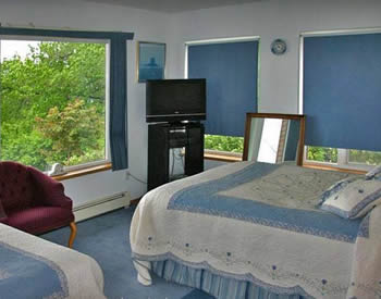Shows room with large windows on two sides, and two queen-sized beds with blue and white bedspreads.