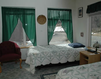 Shows room with windows on two walls and two beds with green and white bedspreads and a burgundy chair.