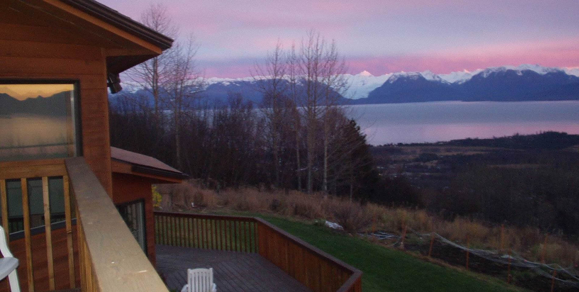 View from the rose room balcony showing the yard and a bright pink sunset over snow-capped mountain peaks
