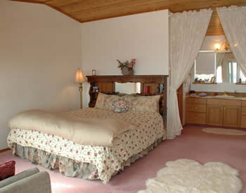 Shows room with king bed, white walls, pink carpeting, lace curtains, and the bathroom vanity and mirror.